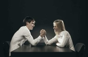 Man and woman in a contested divorce arm wrestling at a table.