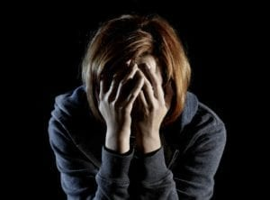 Woman dealing with heartbreak holding her face in her hands