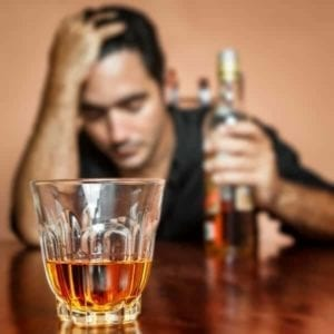 Close up of a whiskey glass with a man trying to deal with heartbreak holding a whiskey bottle and looking depressed in the background