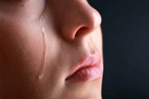 Close up of a woman with a tear running down her cheek as she is wondering how to deal with heartbreak