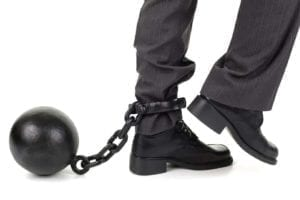 Businessman with ball and chain around his ankle