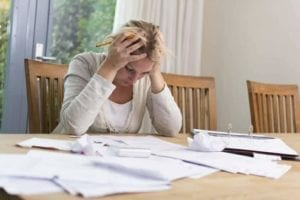 Upset woman looking at paperwork with her head inher hands