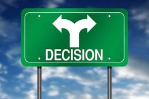 Green sign with white arrows pointing in both directions signifying confused decision.