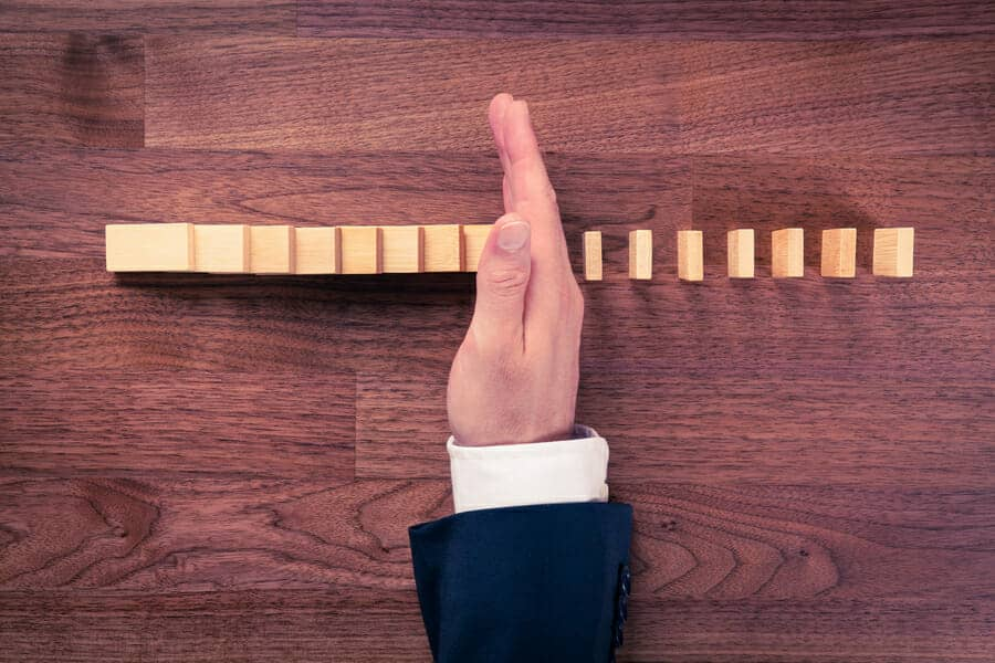 Hand stopping a line of dominoes. Divorce strategies to stop the damage.