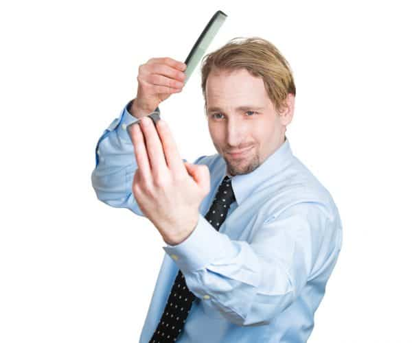Narcissistic man combing his hair and gazing into a mirror. How to win when divorcing a narcissist?