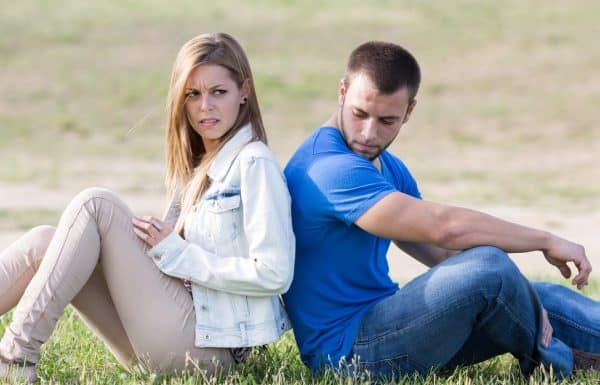 Upset married couple sitting back to back thinking about a trial separation.