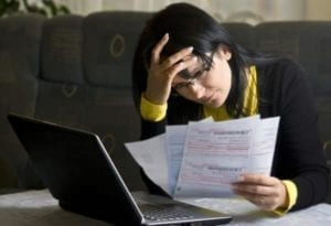 Frustrated woman reviewing tax returns trying to figure out the alimony tax deduction.