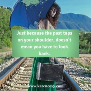 Woman with a suitcase walking on railroad tracks with quote don't look back.