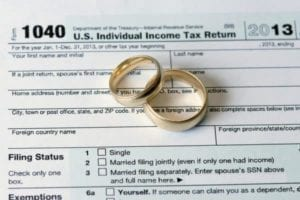 Wedding rings on tax return signifying divorce and taxes.