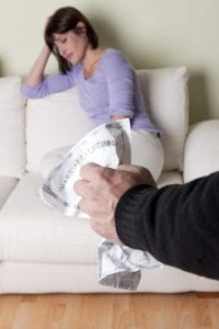Upset woman facing divorce and sitting on a couch with husband's hand in foreground crunching their marriage license.