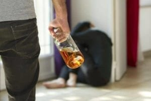 Man with whiskey bottle walks toward cowering wife: Domestic violence scene