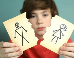 Sad boy whose parents are fighting over equal parenting time holding up torn stick figure picture of parents