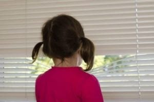 Sad girl looking between blinds, waiting for her dad to pick her up for shared parenting time.