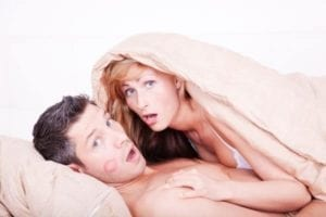 Surprised cheating couple in bed now dealing with alimony, infidelity and divorce