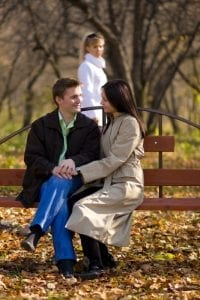 Loving couple in the park with a jealous woman looking on in the background. Infidelity and divorce concept.