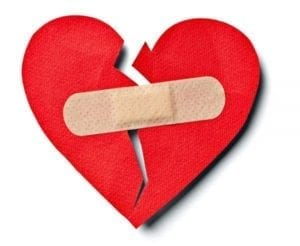 Broken red paper heart with a band aid on it designating reconciling with your ex