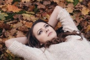 Beautiful woman laying in a pile of fall leaves wondering about the best advice for divorcing women
