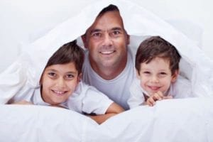 Smiling picture of Dad and his boys hiding under the covers in a white bed