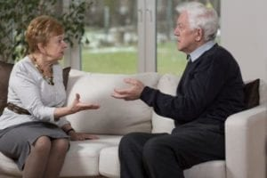 Senior couple going through a gray divorce arguing on a couch