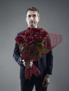 Man with exasperated smile holding a dozen roses. Don't date during divorce!