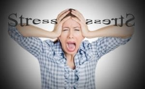 "Woman screaming and holding her head with the word ""Stress"" stretched behind her. How to reduce divorce stress?"