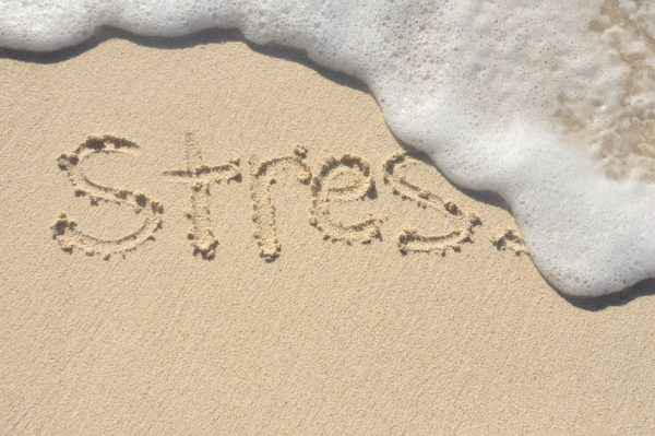 """Word """"Stress"""" written in sand being washed away by the ocean."""