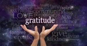 Hands opening to a word cloud of gratitude on a starry purple background