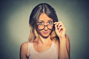 Young woman thinking about alimony in Illinois looking down over big glasses