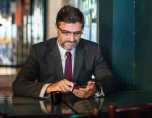 Middle aged male lawyer on social media on his phone