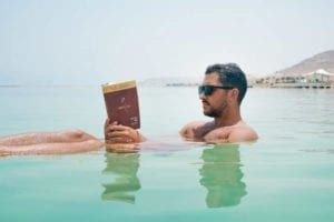 Handsome man with sunglasses floating in tropical water reading a book.