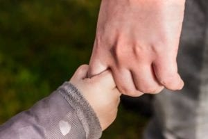 Close up of parent's hand holding a todler's hand. Parenting.