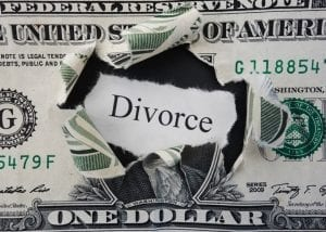Close up of dollar bill with a whole torn in the middle and the word Divorce, signifying the cost of divorce.