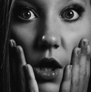 Black and white photo of a beautiful surprised woman who didn't understand the danger of a cheap divorce.