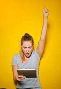Woman hooting with her arm up in front of a bright yellow background! Time for a divorce party!