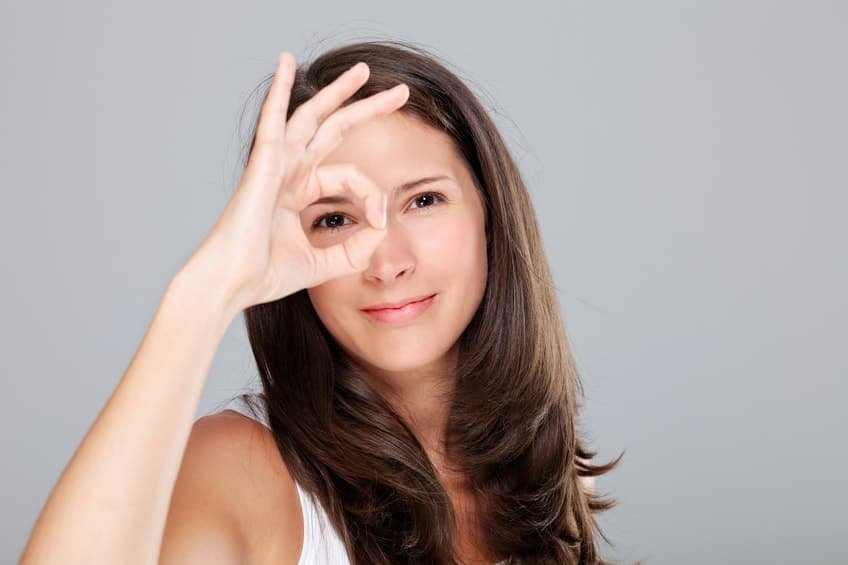 Woman looking through a circle made with her fingers demonstrating focus.