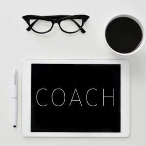 "Black glasses, coffee cup and ipad with the word ""Coach"" on it, symbolizing ""Coaching."""