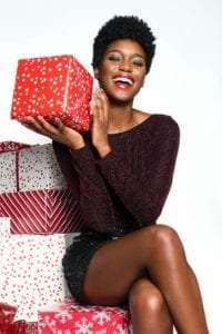 Smiling, beautiful African American woman in sparkling dress sitting next to a pile of divorce gifts and holding one up.
