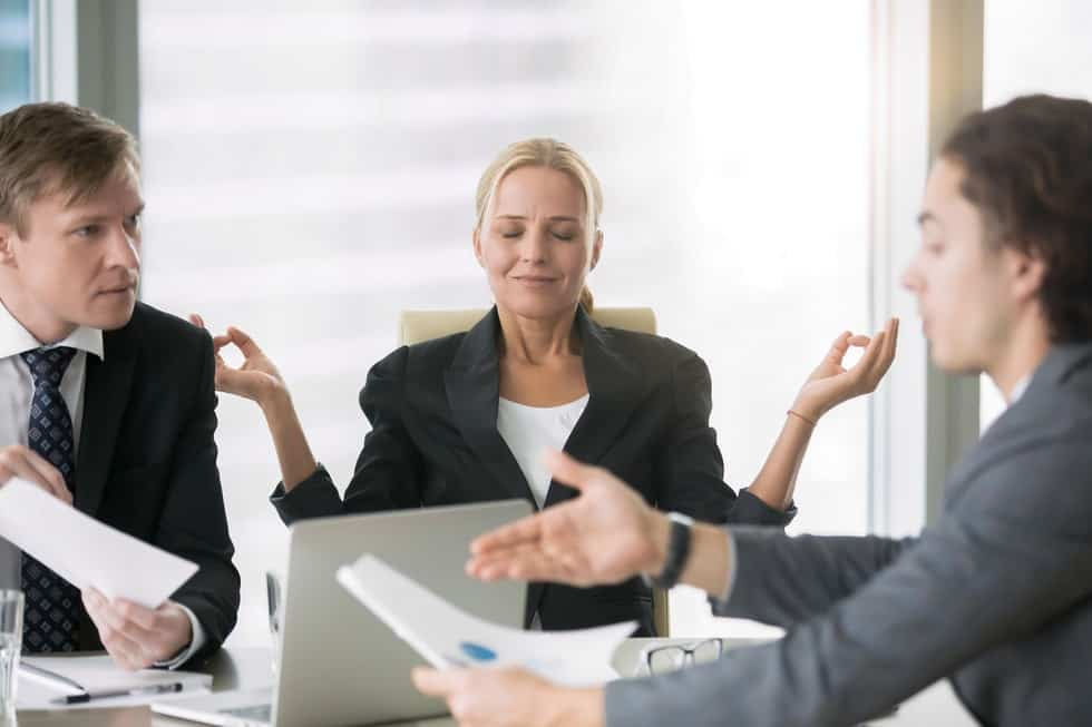 Female mediator using divorce mediation tips is meditating while two male lawyers argue.
