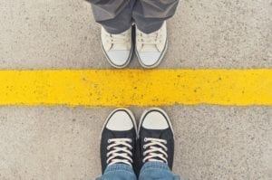 Close up of two people in sneakers standing toe to toe on opposite sides of a yellow line. Signifies mediation strategies.