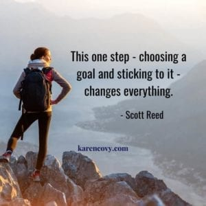 Woman hiker standing on a mountain top with the quote: This one step- choosing a goal and sticking to it - changes everything. How to Set Goals for Your Divorce.