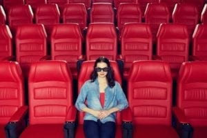 Woman alone on Valentine's Day sitting by herself in a movie theatre of red seats.