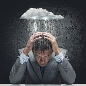 Depressed businessman dealing with divorce stigma has a rain cloud making a thunderstorm over his head.