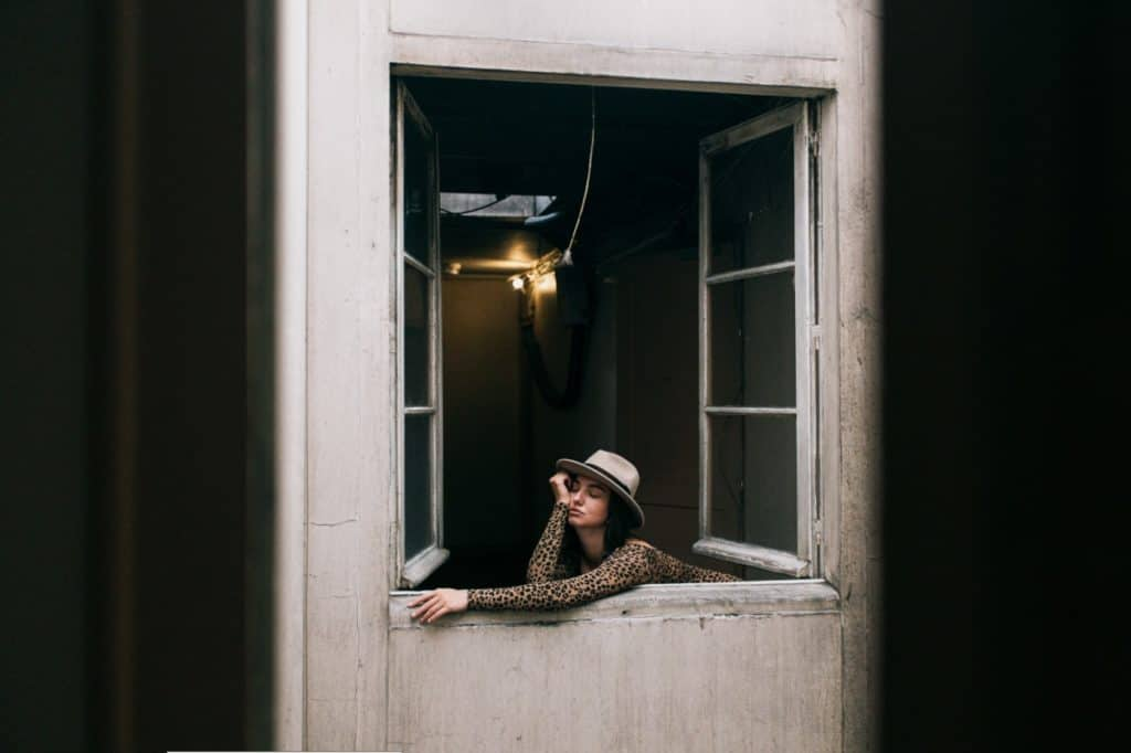 Bored woman looking out an open apartment window trying to escape her marriage during quarantine.