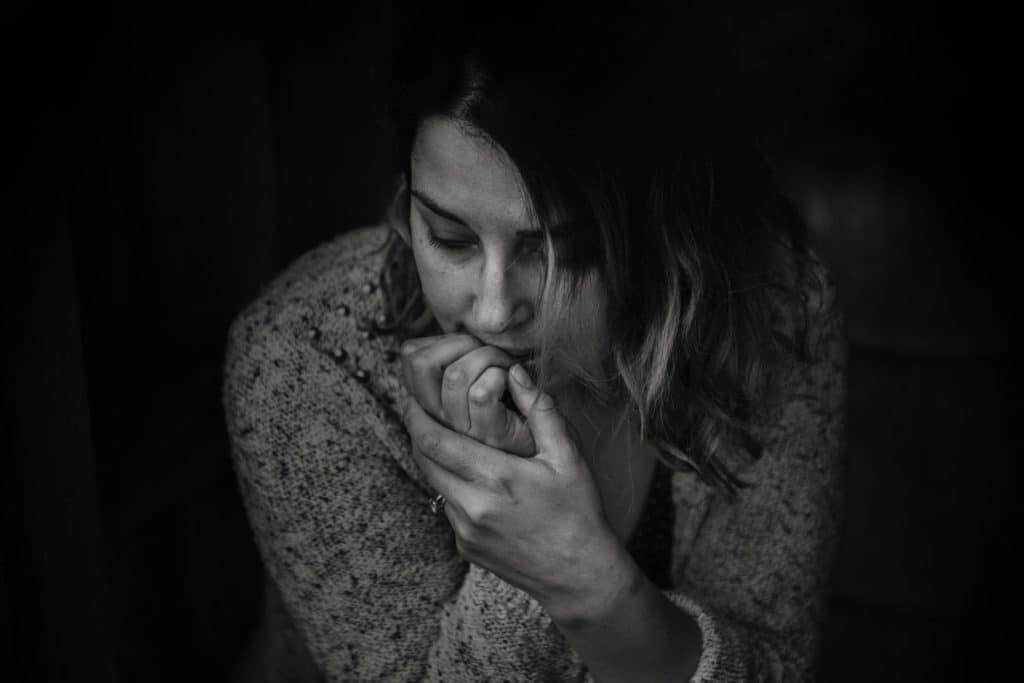 Black and white picture of a a woman with anxiety biting her nails.