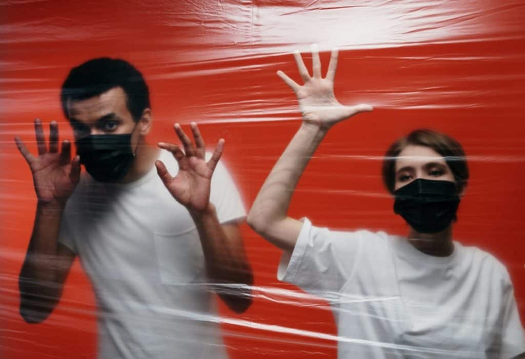 Man and woman in white t-shirts and black masks behind a wall of plastic are co-parenting during quarantine.