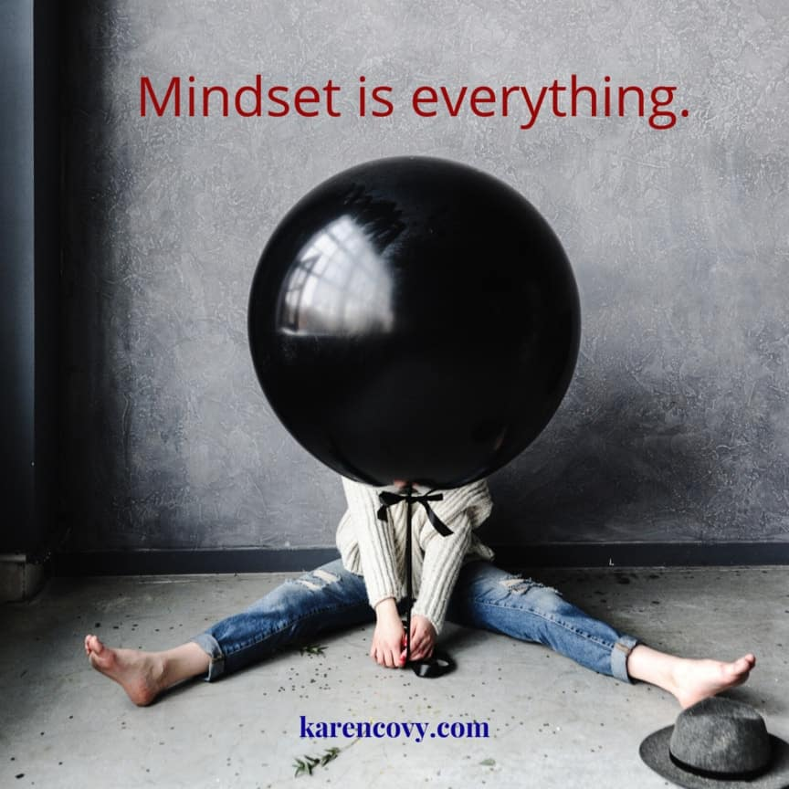 Woman with giant black balloon in front of her head with saying: Mindset Matters. Mindset is everything.